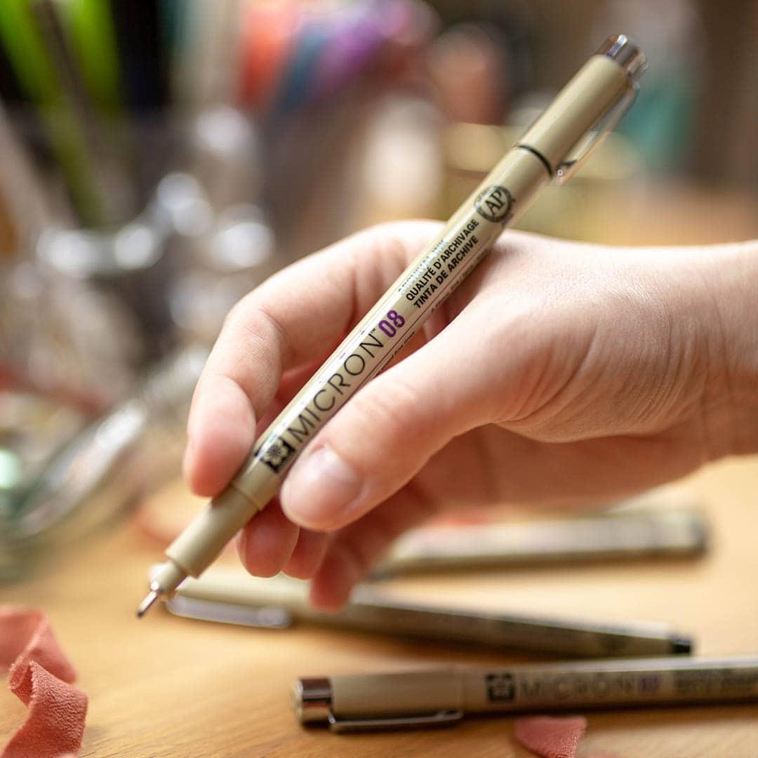 hand holding a Sakura Pigma pen