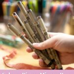 hand holding Sakura Pigma Micron Pens with text overlay