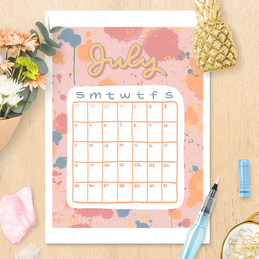 July calendar printable with bright, colorful splash design sitting on wooden desk with flowers, gemstones, and other decor items.