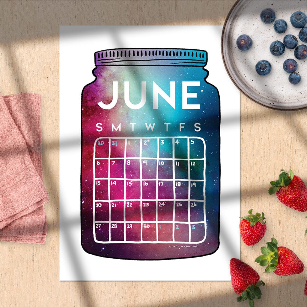 June printable on wood desk with strawberries and plate of blueberries.