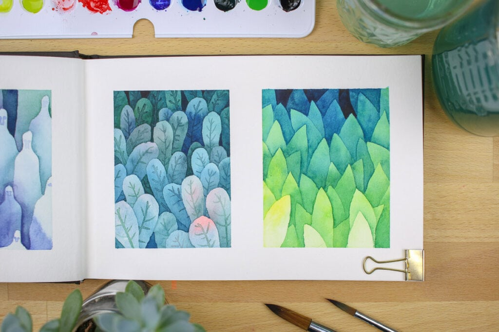 Open watercolor journal showing two small paintings of layered leaves.