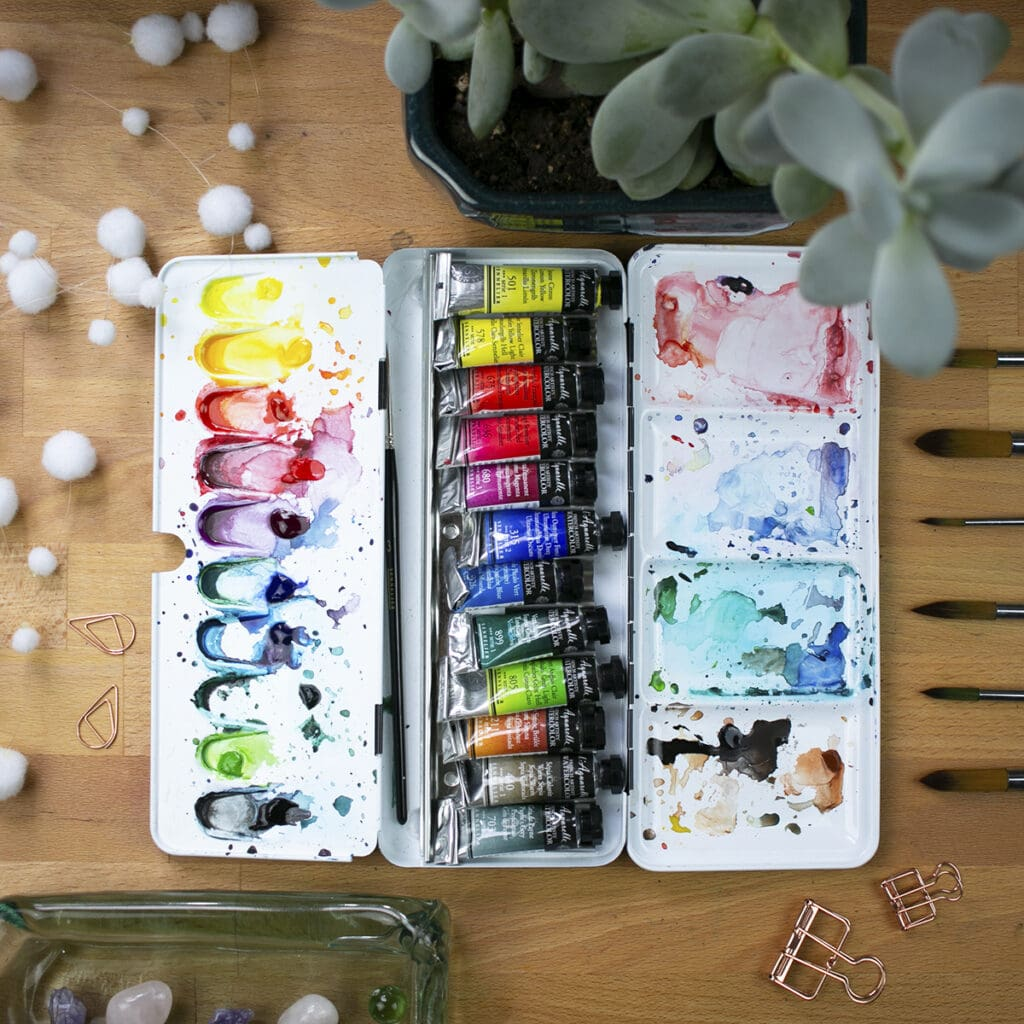 Messy palette of sennelier watercolor tubes sitting on desk with houseplants and brushes.