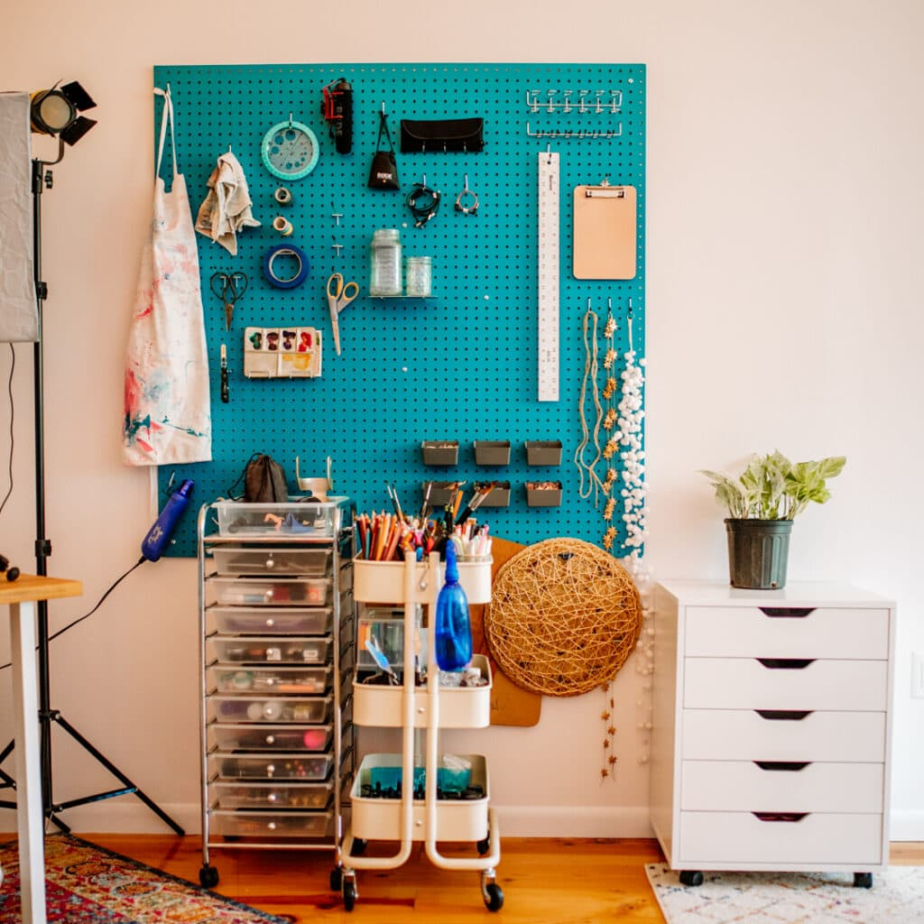 Teal peg board with art supplies and film equipment hanging over two carts full of art supplies.