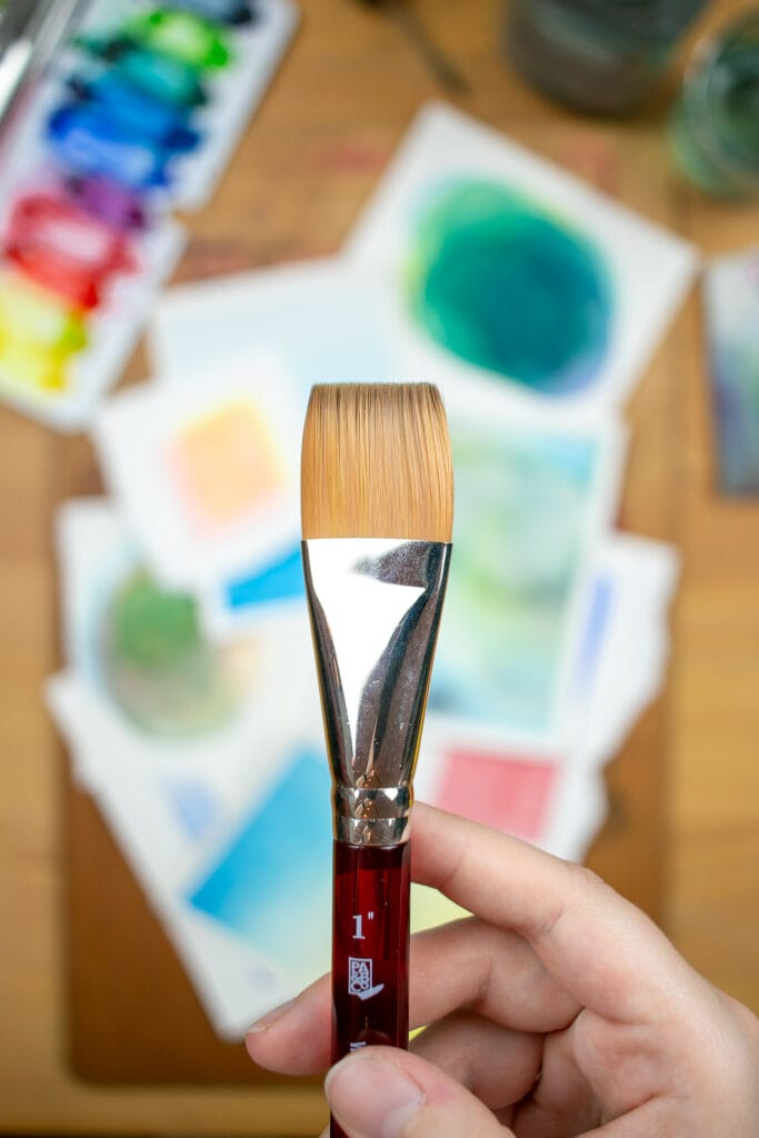 Hand holding flat paintbrush over desk with small watercolor paintings and supplies.