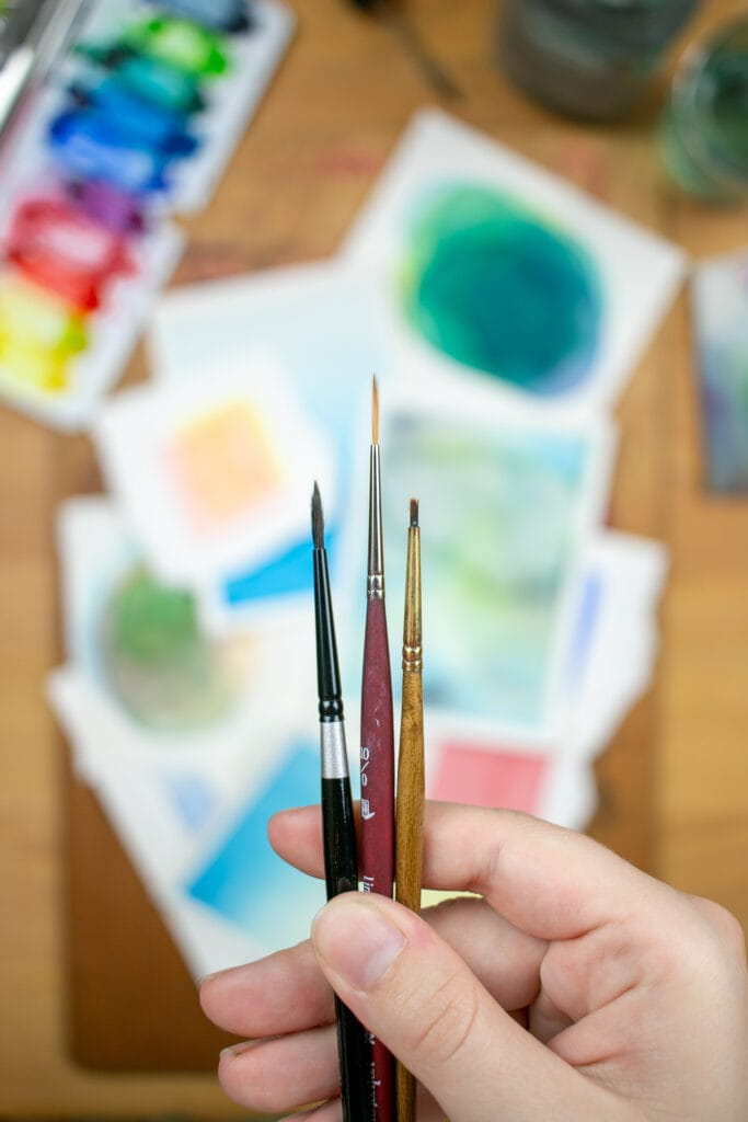 Hand holding detail paintbrushes over desk with small watercolor paintings and supplies.