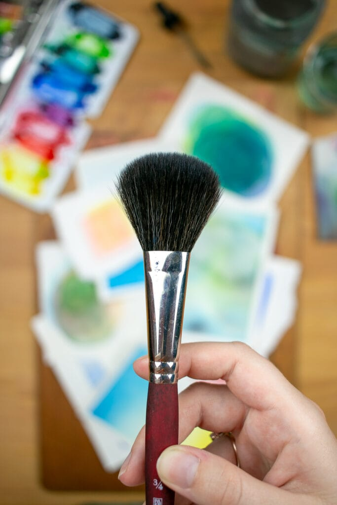 Hand holding mop paintbrush over desk with small watercolor paintings and supplies.