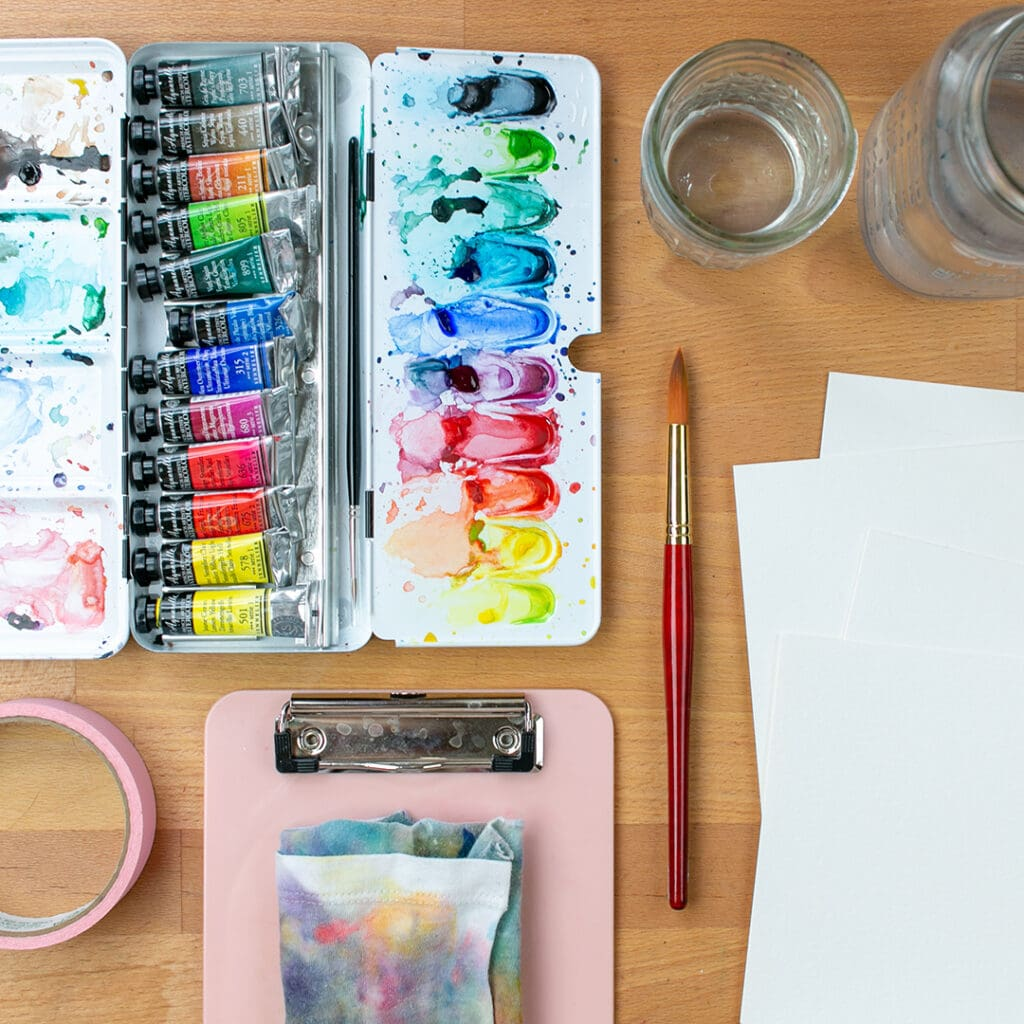 Flatlay of watercolor supplies on desk, including paper, brush, rag, palette, and tape.