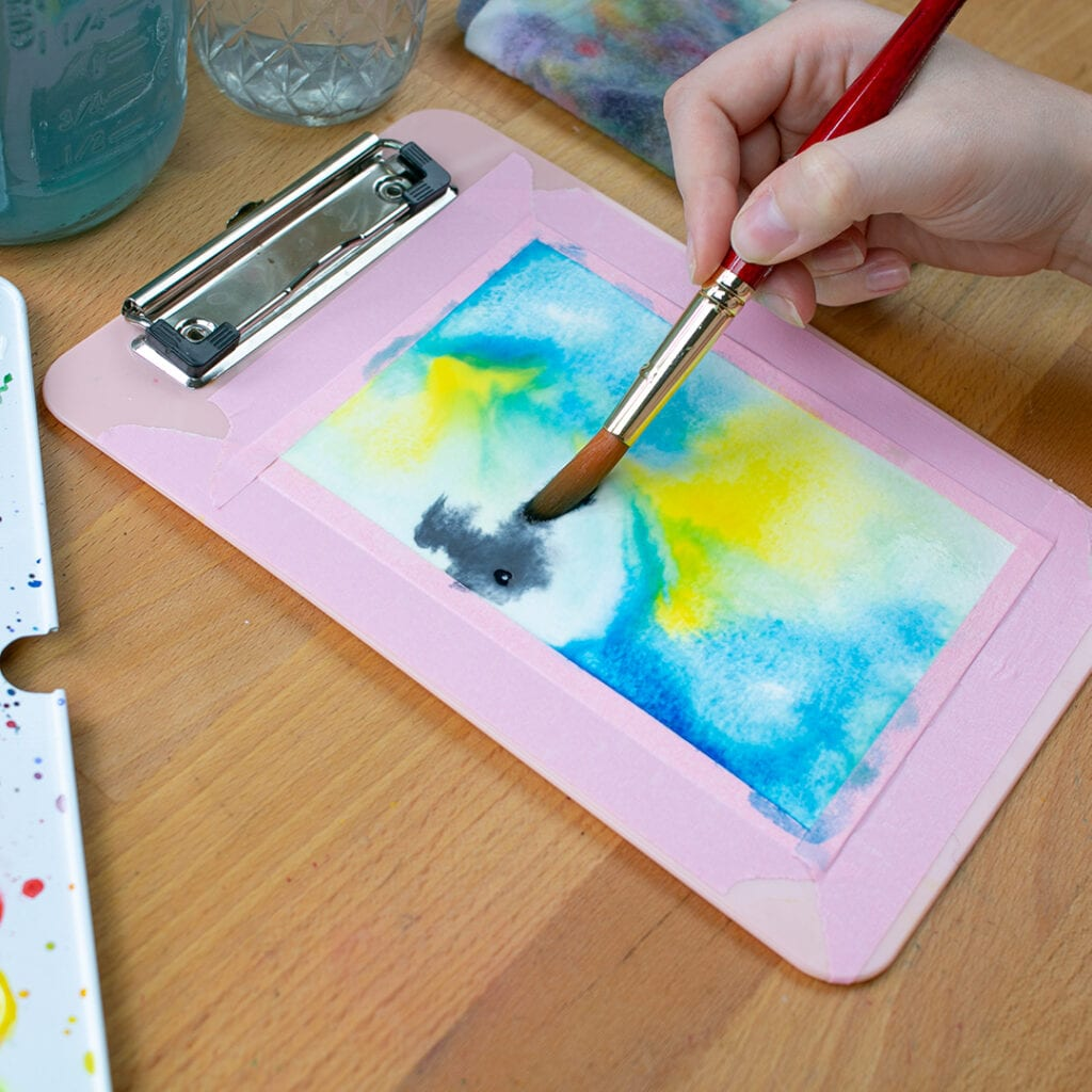 Small clipboard with watercolor painting in progress.