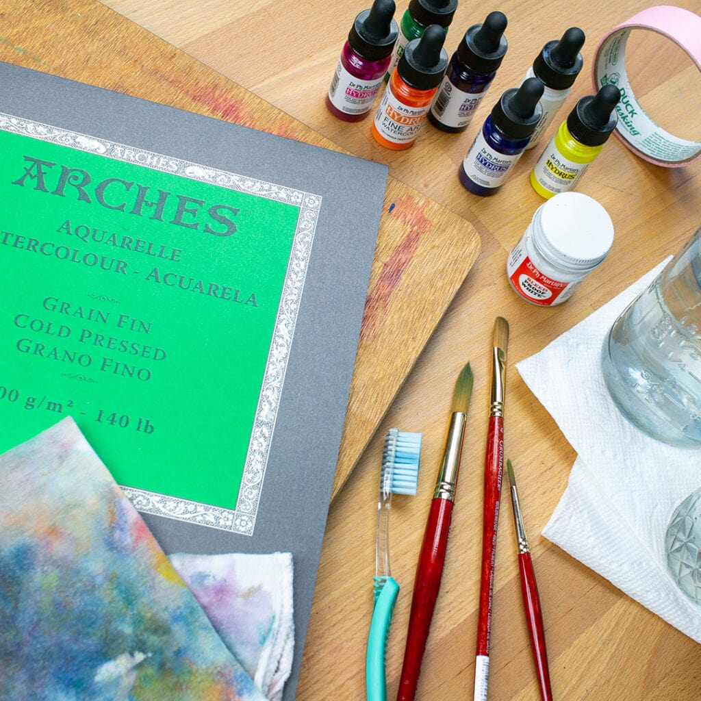 Watercolor supplies on desk, including paper, liquid paint bottles, brushes, water jars, and rag.