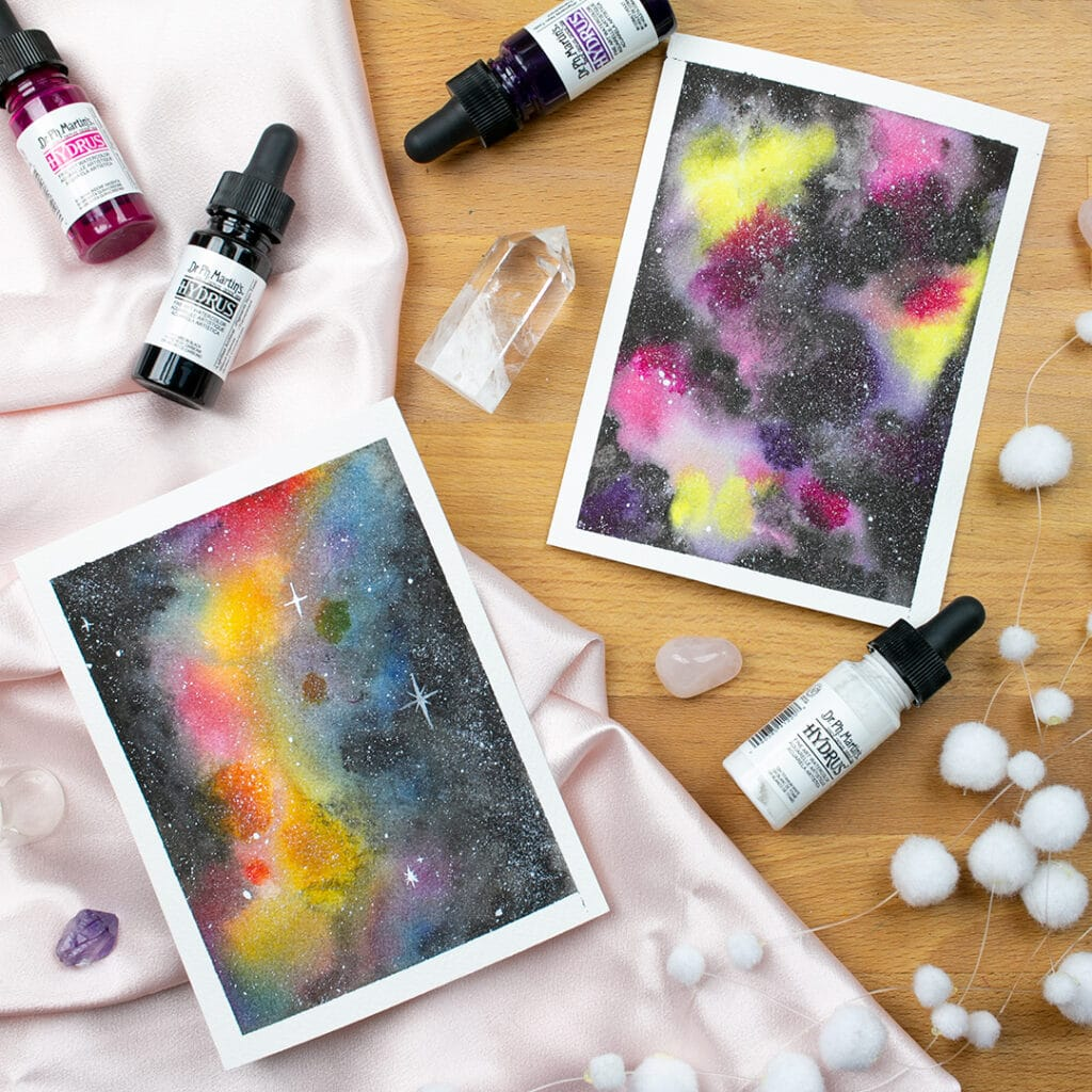 Two small paintings of watercolor galaxies laying on desk surrounded by art supplies.