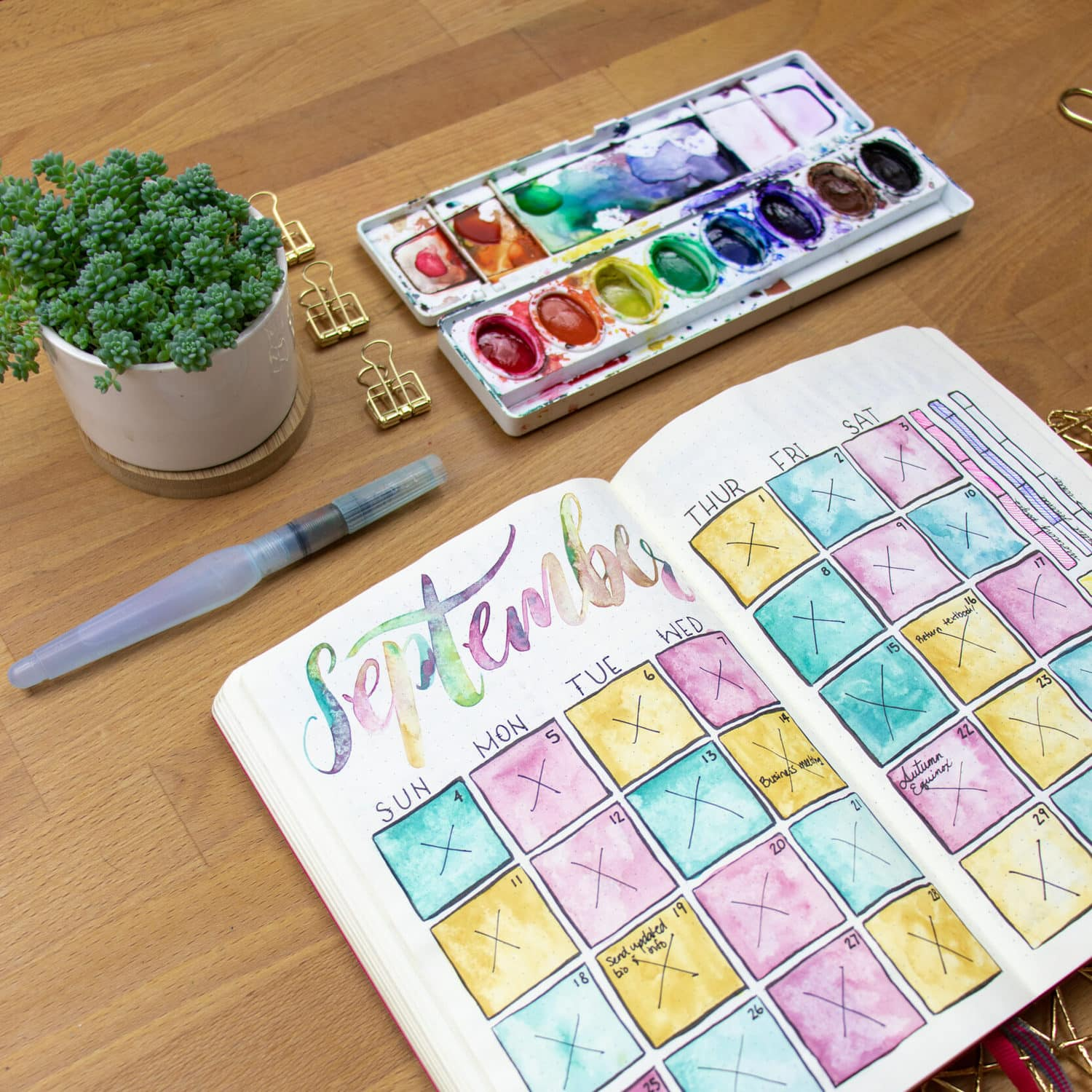Journal open to watercolor calendar with prang watercolor palette open on desk.