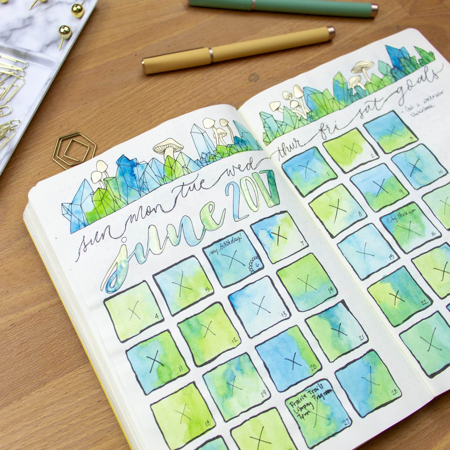 Open journal with watercolored blue and green calendar sitting on desk.
