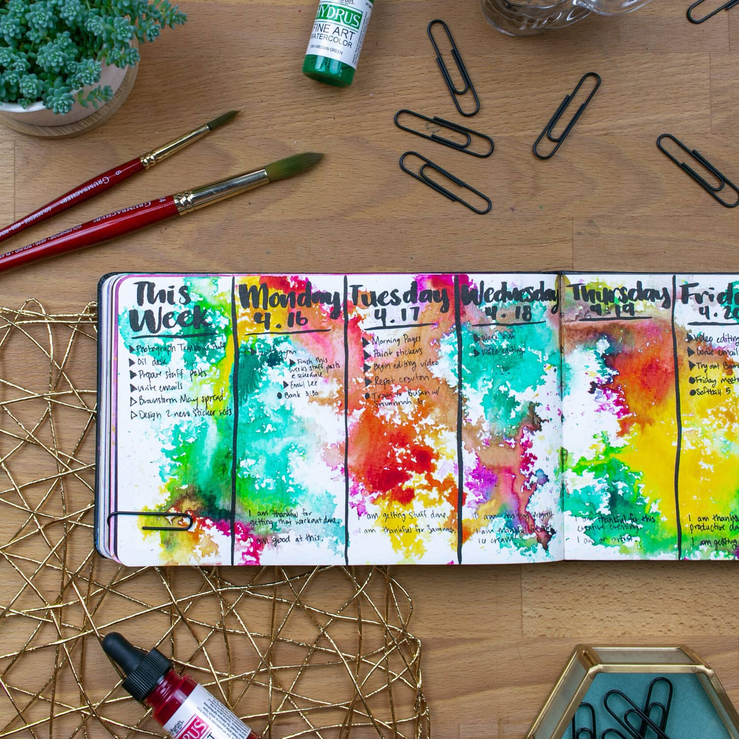 Open journal on desk with vibrant watercolor splashes, desk is covered in various office supplies.