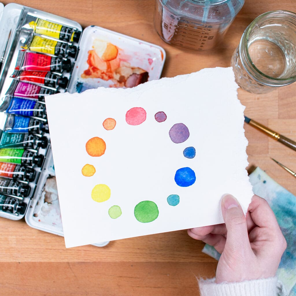 Hand holding watercolor paper with painted color wheel over a palette of paints.