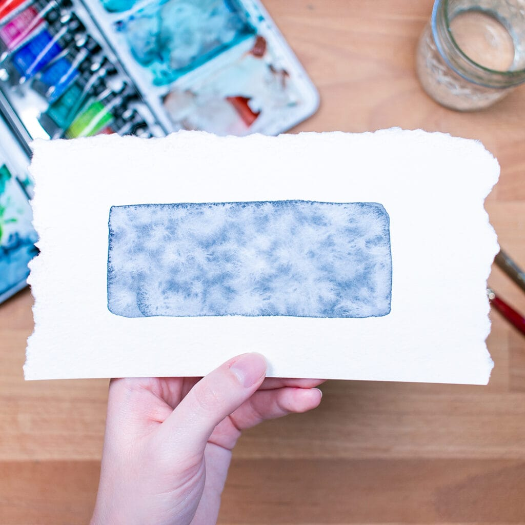 Hand holding watercolor paper above desk with blue rectangle painted on it.